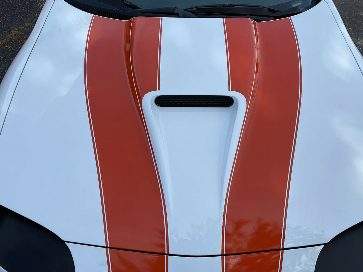 White 1997 Chevy Camaro SS with red stripes on the hood